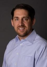 Image of Dan Weisman in a blue shirt with a grey background, looking right at the camera.