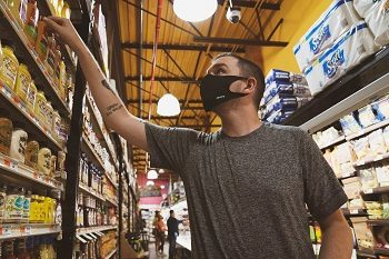 Man wearing a mask in a grocery store reaching the shelf