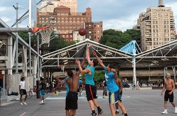 Kids playing in a basketball court in New York city