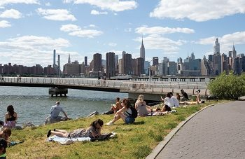 People sunbathing along the river bank in NYC
