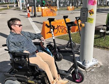 Woman in wheelchair next to parked scooters