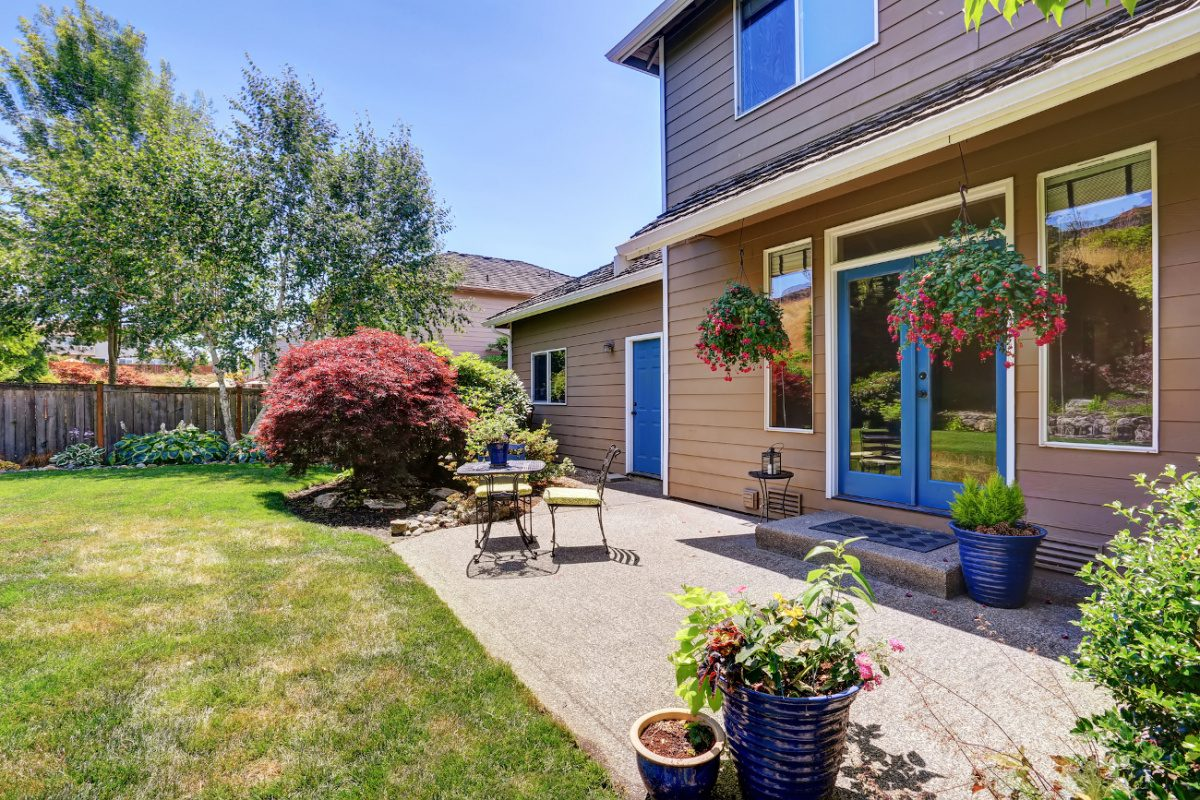 2 story house with backyard patio, blue trim and green lawn.