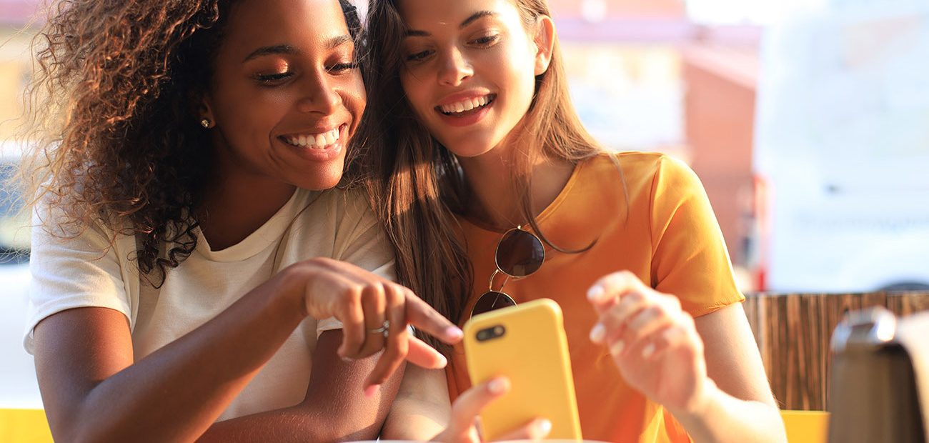Two Women Smiling at Smartphone