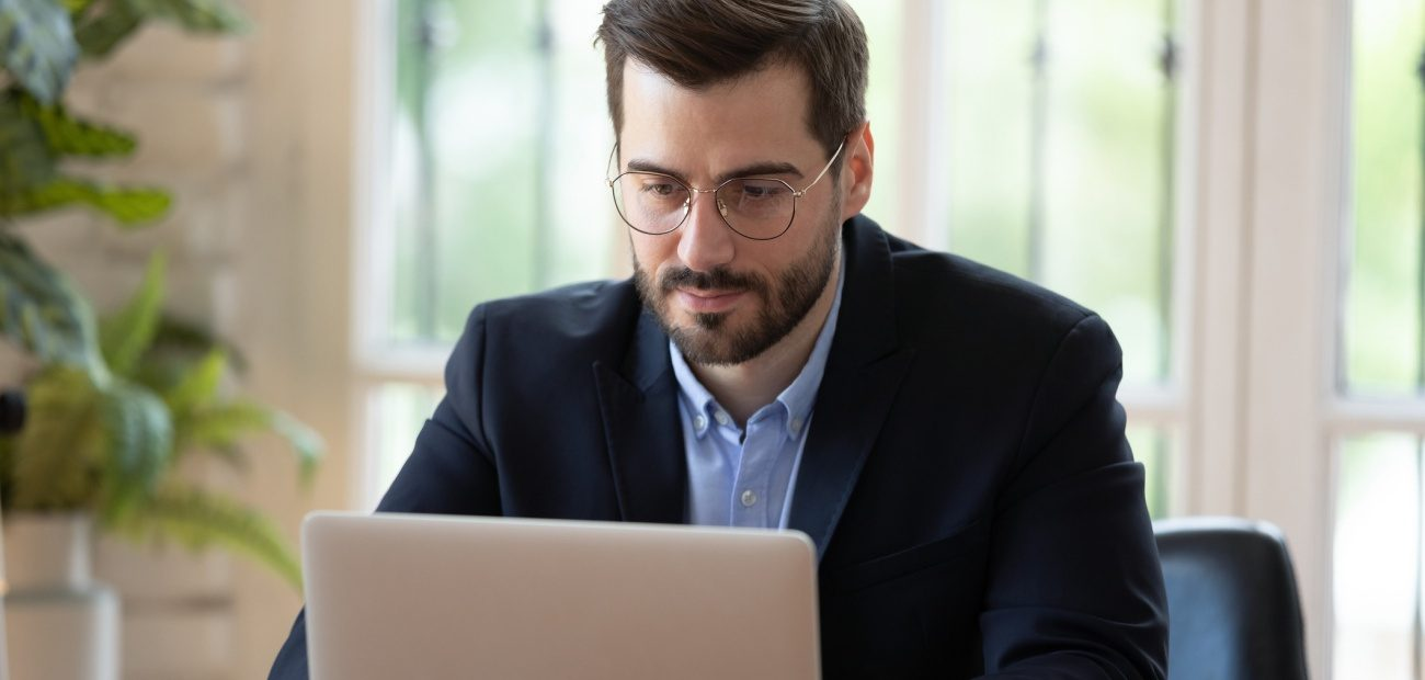 Head shot concentrated young businessman working with computer at office