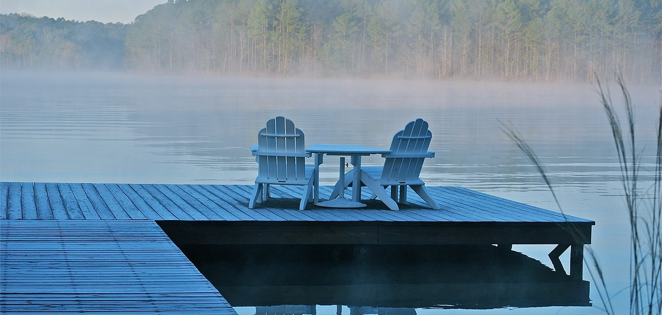 Adirondack chairs and table on lake dock