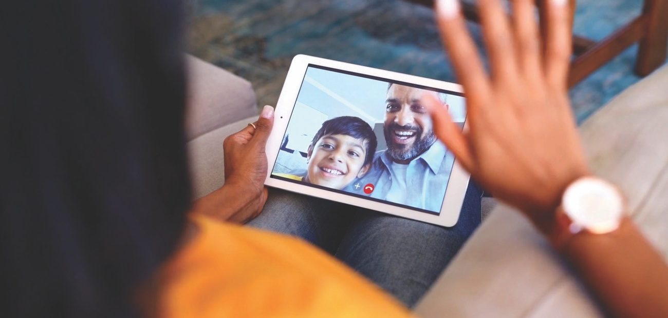 Woman waving at family from mobile tablet