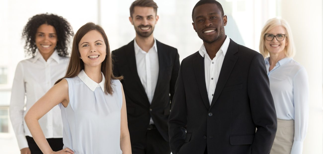 Group of people posing for portrait in business attire.