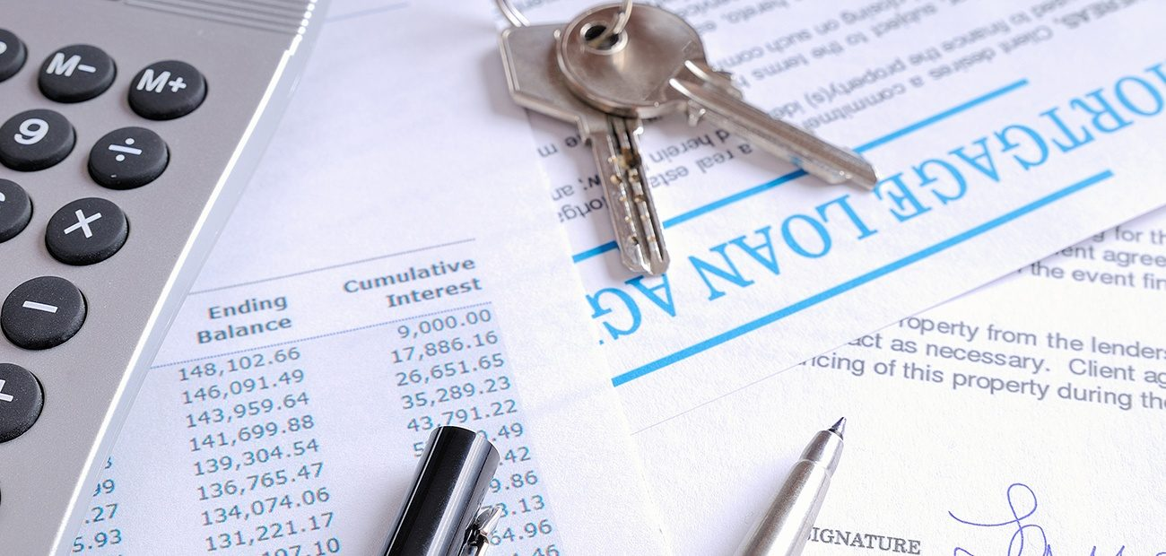 Mortgage papers, keys, calculator, and pens
