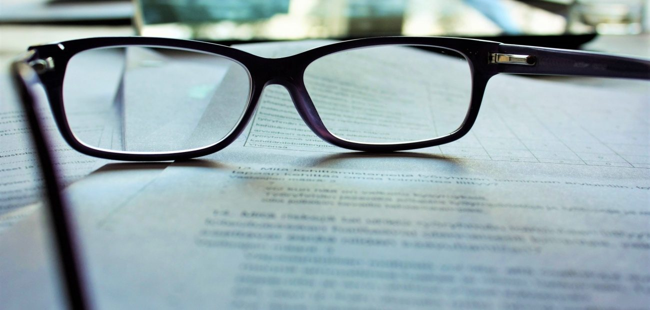 Reading glasses sitting on top of paperwork