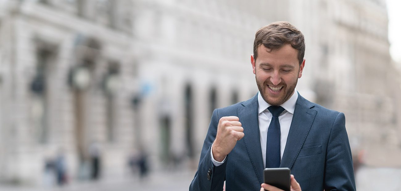 Fist pumping man on smartphone