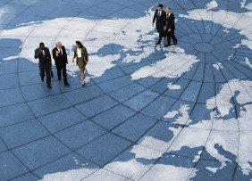 Business professionals walking across a world map floor