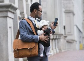 Businessman on the street carrying a briefcase, a phone, and a baby