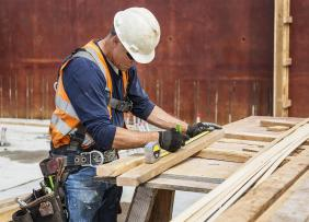 Construction worker measuring wood