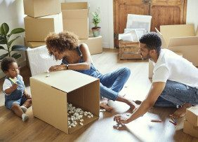Family packing boxes on living room floor