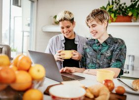 Female couple in the kitchen, looking at a laptop