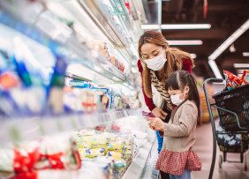 Mother and child wearing masks and grocery shopping