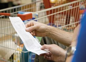 People holding a receipt with shopping cart in the background