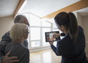 Agent and clients in an empty house using a tablet