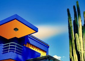 Royal blue house with orange accents and cactus
