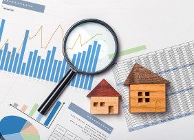 Wooden houses and magnifying glass on spreadsheets