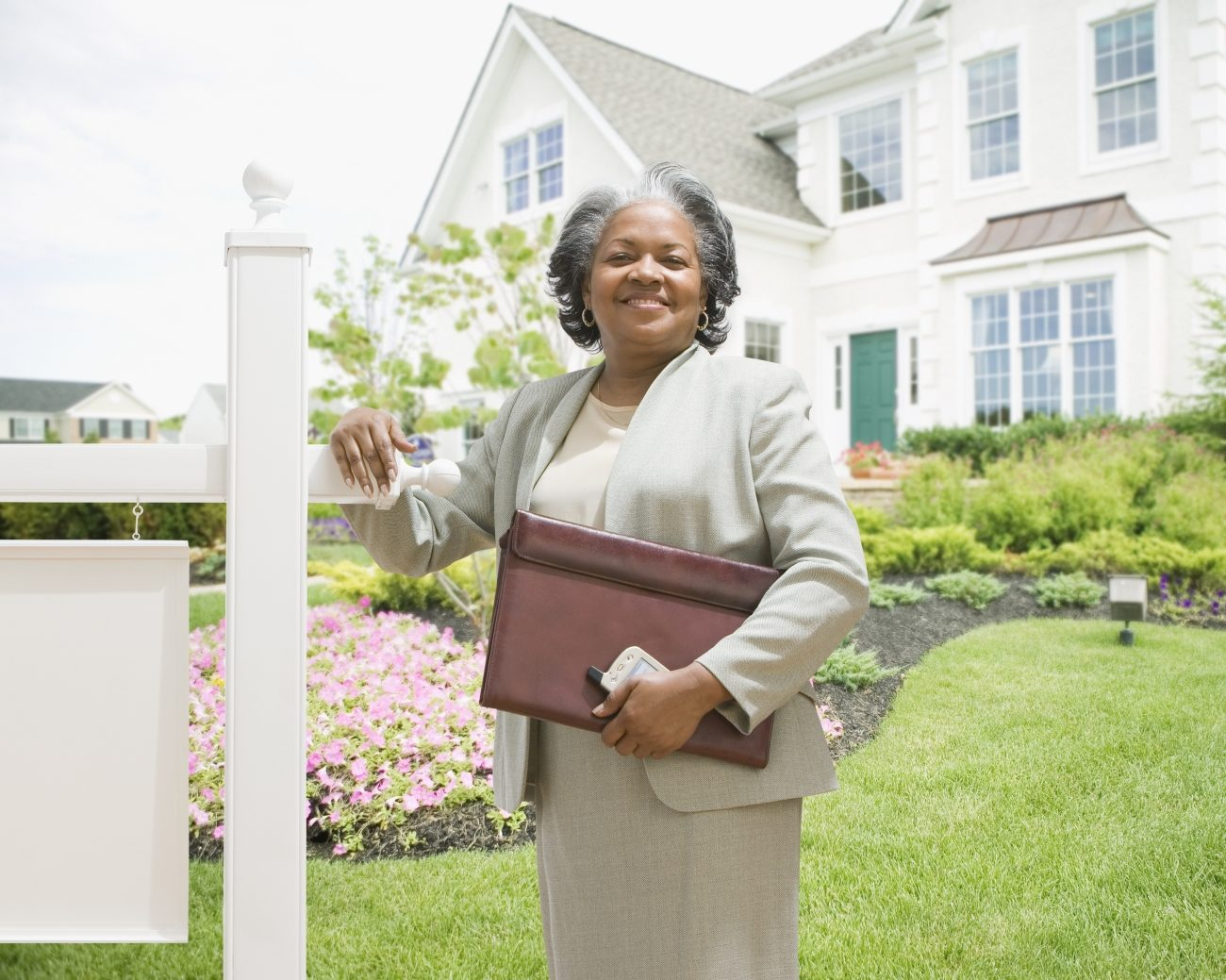 A woman standing in front of a house for sale sign, holding a briefcase and phone